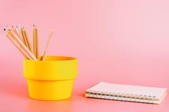 Färben Sie Bleistifte im Eimer mit Notizbuch auf Rosa Stockbilder