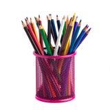 Färben Sie Bleistifte im roten Metallgitterbehälter, der auf Weiß lokalisiert wird Stockfotos