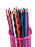 Färben Sie Bleistifte im roten Metallgitterbehälter, der auf Weiß lokalisiert wird Stockbilder