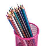 Färben Sie Bleistifte im roten Metallgitterbehälter, der auf Weiß lokalisiert wird Lizenzfreie Stockfotos