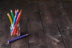 Färben Sie Bleistifte im Standhalter auf dem hölzernen Weinlesehintergrund Lizenzfreies Stockbild