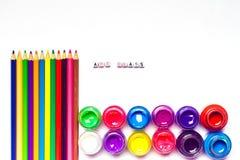 Färben Sie Bleistifte mit Aquarellfarben und leere Räume auf Weiß Stockfotos