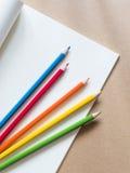 Färben Sie Bleistifte mit einem Buch auf braunem Hintergrund Stockbilder