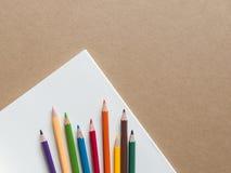 Färben Sie Bleistifte mit einem Buch auf braunem Hintergrund Stockfotos