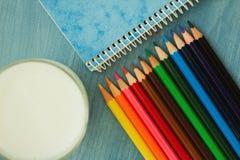 Färben Sie Bleistifte mit einem Notizbuch und einem Glas Milch Stockbilder