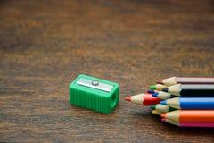 Färben Sie Bleistifte mit grünem Bleistiftspitzer auf dem hölzernen Hintergrund Stockfotos