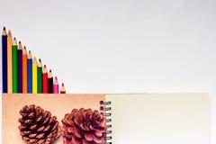 Färben Sie Bleistifte mit Notizbuch und leere Räume auf weißem backgroun Lizenzfreie Stockfotos