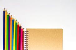 Färben Sie Bleistifte mit Notizbuch und leere Räume auf weißem backgroun Lizenzfreie Stockfotografie