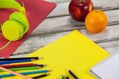 Färben Sie Bleistifte, Notizblock, Plakat, Früchte und Kopfhörer Lizenzfreies Stockfoto