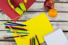 Färben Sie Bleistifte, Notizblock, Plakat, Früchte und Kopfhörer Stockfoto