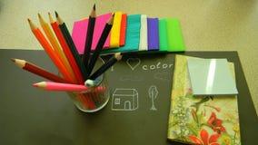 Färben Sie Bleistifte, Notizbuch für Kreativität auf einem schwarzen Hintergrund Stockfoto