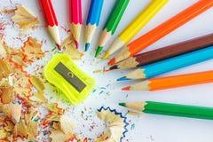 Färben Sie Bleistifte, Schnitzel von den Bleistiften und einen Bleistiftspitzer Lizenzfreie Stockfotos