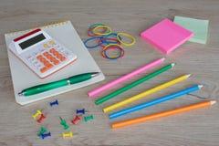 Färben Sie Bleistifte, Taschenrechner, Notizbuch und Büroartikel, Geschäftszubehör auf Holztisch Lizenzfreies Stockfoto
