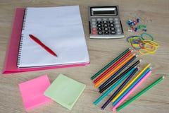 Färben Sie Bleistifte, Taschenrechner, Notizbuch und Büroartikel, Geschäftszubehör auf Holztisch Stockbild
