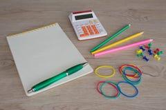 Färben Sie Bleistifte, Taschenrechner, Notizbuch und Büroartikel, Geschäftszubehör auf Tabelle Stockfoto