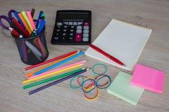 Färben Sie Bleistifte, Taschenrechner, Notizbuch und Büroartikel, Geschäftszubehör auf Tabelle Stockfotografie