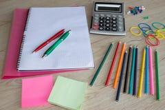 Färben Sie Bleistifte, Taschenrechner, Notizbuch und Büroartikel, Geschäftszubehör auf Tabelle Lizenzfreie Stockfotos