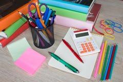 Färben Sie Bleistifte, Taschenrechner, Notizbuch und Bürobriefpapier bei Tisch Geschäftszubehör auf Tabelle Lizenzfreie Stockfotografie
