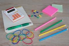 Färben Sie Bleistifte, Taschenrechner, Notizbuch und Bürobriefpapier bei Tisch Geschäftszubehör auf Tabelle Lizenzfreies Stockbild