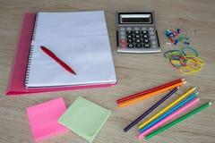 Färben Sie Bleistifte, Taschenrechner, Notizbuch und Bürobriefpapier bei Tisch Geschäftszubehör auf Tabelle Lizenzfreie Stockbilder