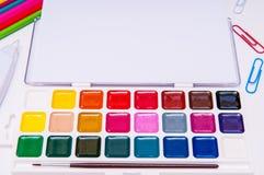 Färben Sie Bleistifte und Aquarelle auf weißem Hintergrund, zurück zu Schule, Briefpapier mit leerem Raum Lizenzfreie Stockfotos