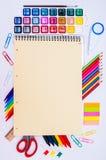 Färben Sie Bleistifte und Aquarelle mit gelbem Notizbuch auf weißem Hintergrund, zurück zu Schule, Briefpapier Stockfotografie