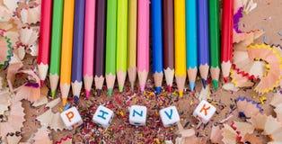 Färben Sie Bleistifte und Buchstabewürfel auf Bleistiftschnitzeln Stockfotografie