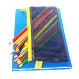 Färben Sie Bleistifte und ein Blue Noten-Buch, das auf weißem Hintergrund lokalisiert wird Lizenzfreie Stockfotografie