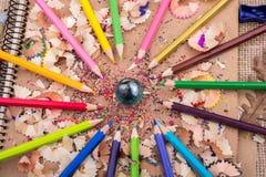 Färben Sie Bleistifte und einen Marmor auf Bleistiftschnitzeln Lizenzfreie Stockfotografie