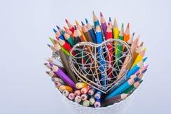 Färben Sie Bleistifte und Herz geformten Metalldrahtkäfig Lizenzfreie Stockbilder