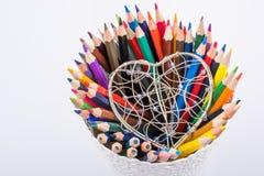 Färben Sie Bleistifte und Herz geformten Metalldrahtkäfig Lizenzfreie Stockfotografie