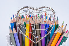 Färben Sie Bleistifte und Herz geformten Metalldrahtkäfig Stockbilder