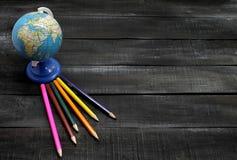 Färben Sie Bleistifte und Kugel auf einem hölzernen Hintergrund mit Raum für Text Stockfoto