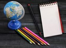 Färben Sie Bleistifte und Kugel auf einem hölzernen Hintergrund mit Raum für Text Lizenzfreie Stockfotografie