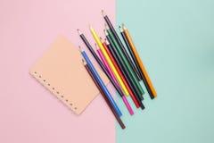Färben Sie Bleistifte und Notizbuch auf einem farbigen Hintergrund Lizenzfreie Stockfotos