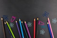Färben Sie Bleistifte und verschiedene Büroklammern auf dunklem Hintergrund Stockbild
