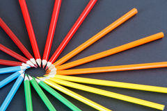 Färben Sie Bleistifte vereinbart in einem Kreisoben links auf dunklem Hintergrund, Draufsicht Stockfoto