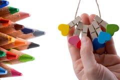 Färben Sie Bleistifte von verschiedenen Farb- und Dominostücken Stockbild