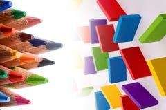 Färben Sie Bleistifte von verschiedenen Farb- und Dominostücken Lizenzfreie Stockfotos