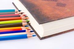 färben Sie Bleistifte von verschiedenen Farben nahe dem heiligen Quran Stockfotografie
