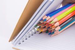 färben Sie Bleistifte von verschiedenen Farben nahe einem Notizbuch Stockfotos
