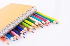 färben Sie Bleistifte von verschiedenen Farben nahe einem Notizbuch Lizenzfreie Stockfotos