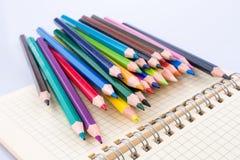 färben Sie Bleistifte von verschiedenen Farben nahe einem Notizbuch Stockbild