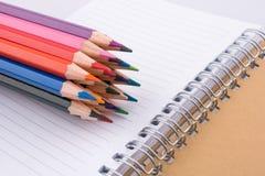 färben Sie Bleistifte von verschiedenen Farben nahe einem Notizbuch Stockbilder