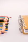 färben Sie Bleistifte von verschiedenen Farben nahe einem Notizbuch Lizenzfreies Stockbild