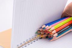 färben Sie Bleistifte von verschiedenen Farben nahe einem Notizbuch Lizenzfreie Stockfotografie