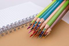 färben Sie Bleistifte von verschiedenen Farben nahe einem Notizbuch Stockfoto