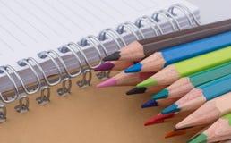 färben Sie Bleistifte von verschiedenen Farben nahe einem Notizbuch Stockfotografie