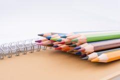 färben Sie Bleistifte von verschiedenen Farben nahe einem Notizbuch Lizenzfreies Stockfoto