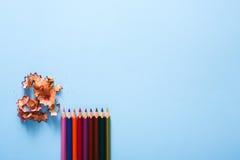 Färben Sie Bleistiftschnitzel auf Blau, Kopienraum, Draufsicht Lizenzfreie Stockfotos